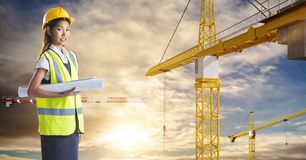 Female architect holding blueprint by cranes against sky Royalty Free Stock Images