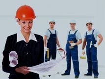 Female architect holding blueprints at the background of the decorators. Stock Image