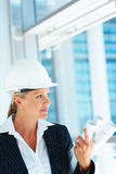 A female architect holding blueprints looking away Royalty Free Stock Photography