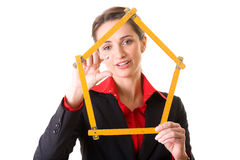 Female architect holds house shape measure tape Stock Image