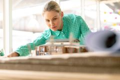 Female architect looking at architectural model. Front view of Caucasian female architect looking at architectural model at desk in office stock image