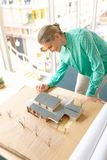 Female architect looking at architectural model. High angle view of Caucasian female architect looking at architectural model at desk in office royalty free stock images