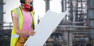 Composite image of female architect looking at blueprint against white background royalty free stock images
