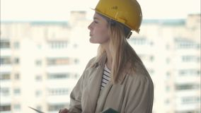 Female architect looking carefully at plan on construction site