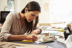Female Architect Making Model In Office. Sitting Down Concentrating Royalty Free Stock Photography