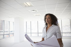 Female Architect In Modern Empty Office Looking At Plans royalty free stock photography