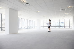 Female Architect In Modern Empty Office Looking At Plans Royalty Free Stock Image