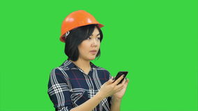 Female architect with orange helmet using smartphone on a Green Screen, Chroma Key. Close up. Professional shot in 4K resolution. 080. You can use it e.g. in stock video