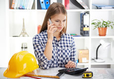 Female architect with phone. Pretty woman architect making estimate of new construction project. Young businesswoman with phone and draft in the office Stock Image