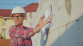 Female architect reading a drawing on a construction site. Young successful professionals royalty free stock image