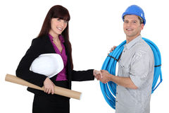Female architect shaking electrician's hand. A female architect shaking electrician's hand Stock Photography