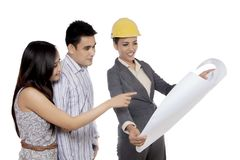 Female architect showing a blueprint to her client stock photos