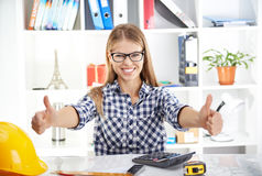 Female architect showing thumb up. Portrait of happy business woman showing thumbs up in the office. Young successful female designer in eyeglasses calculating Royalty Free Stock Images