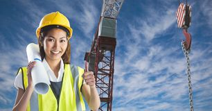 Female architect showing thumbs up against crane Stock Image
