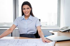 Female Architect Sitting With Blueprints On Desk Stock Image