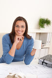 Female architect sitting at office holding coffee Stock Photo