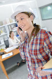 Female architect on speaking to client on phone Royalty Free Stock Image