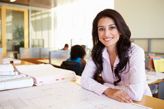 Female Architect Studying Plans In Office. Smiling To Camera Royalty Free Stock Photography