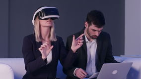 Female architect with VR headset showing blueprints to her male colleague using laptop stock video footage