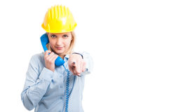 Female architect wearing helmet holding telephone receiver and p Stock Images