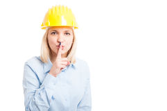 Female architect wearing helmet making sush or silence gesture Stock Photos