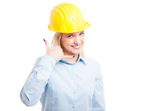 Female architect wearing helmet showing call me gesture Stock Image