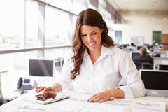 Female architect at work in an office using tablet computer Stock Photo