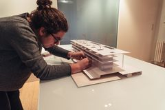 Female architect working on architecture model on table. Female architect working on architecture model made with cardboard on table in office of architectural stock image