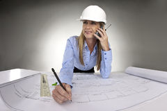 Female architect working on blue prints stock photo