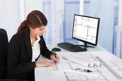 Female architect working on blueprint at desk Stock Images