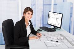 Female architect working on blueprint at desk. Young female architect working on blueprint at desk in office Stock Images