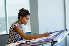 Female architect working on blueprint. In office Royalty Free Stock Photos