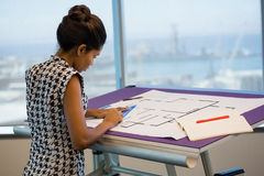 Female architect working on blueprint. In office Royalty Free Stock Photography