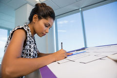 Female architect working on blueprint. In office Stock Photo