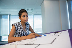 Female architect working on blueprint. In office Stock Image