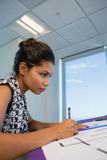 Female architect working on blueprint. In office Royalty Free Stock Photo
