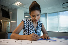 Female architect working on blueprint. In office Stock Photography