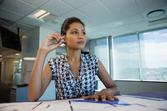 Female architect working on blueprint. In office Stock Images