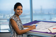 Female architect working on blueprint in office. Portrait of female architect working on blueprint in office Stock Photography
