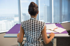 Female architect working on blueprint in office. Rear view of female architect working on blueprint in office Royalty Free Stock Photo