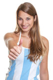 Female argentinian football fan showing thumb. Beautiful woman with long blonde haurs showing thumb in a argentinian jersey on a white background Stock Photos