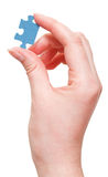 Female arm holding jigsaw puzzle piece Stock Photos