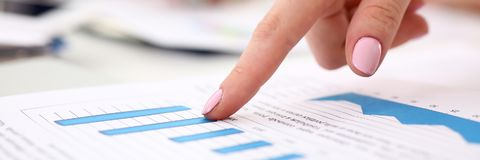 Female arm point finger in financial graph stock photo