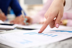 Female arm point pinger in financial graph Royalty Free Stock Photo
