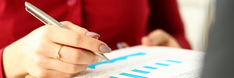 Female arm with silver pen give financial graph papers to client. To discuss problem closeup. Fresh view review situation new angle look professional training stock photos