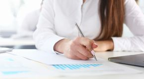 Female arm in suit hold silver pen and pad stock image