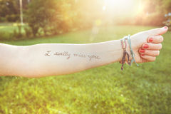 Female arm with text -I really miss you- written. Closeup of female arm with the text -I really miss you- written in the skin over a sunny nature background Royalty Free Stock Image