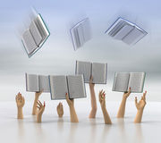 Female arms catching flying books with blur sky Stock Photography