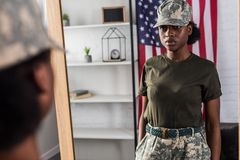 Female army soldier in camouflage clothes posing. By the mirror royalty free stock photo
