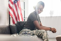 Female army soldier in camouflage clothes sitting. On sofa royalty free stock photo